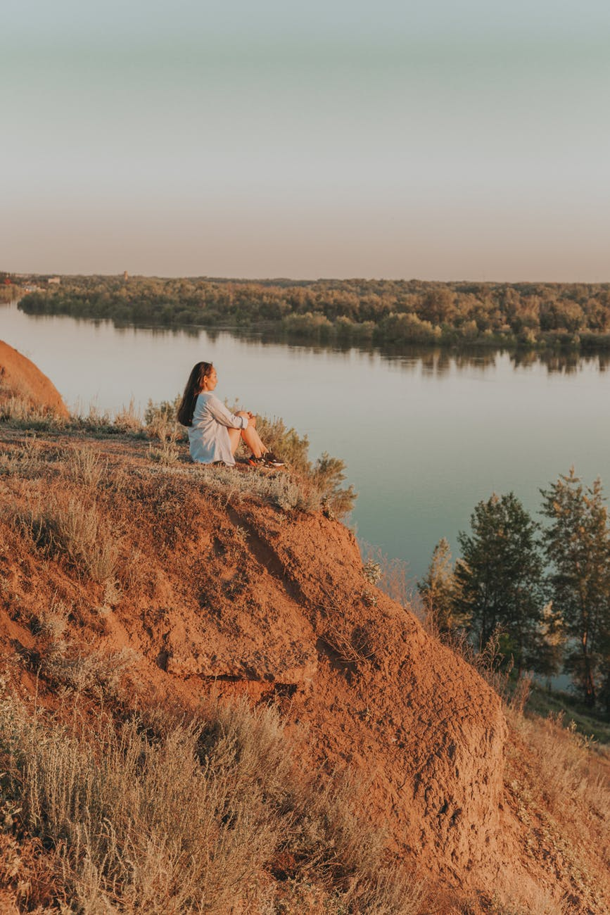 anonymous woman sitting on edge of hill