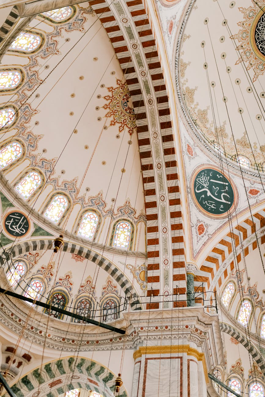 ornamental ceiling of islam medieval mosque with arched windows